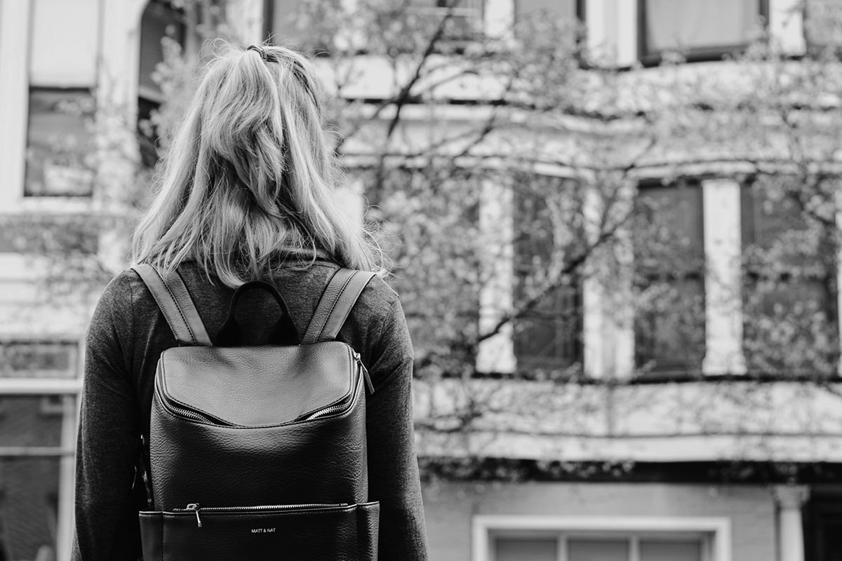 girl with backpack on street scene